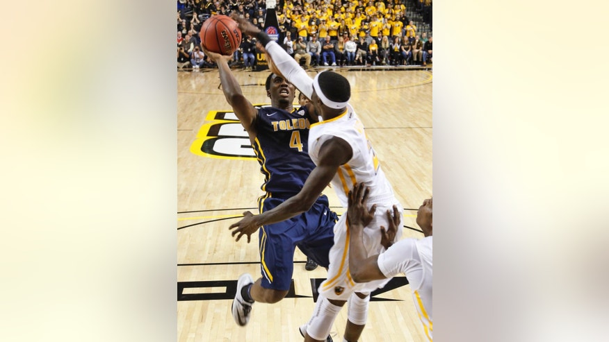 Virginia Commonwealth guard Briante Weber blocks the shot of Toledo guard Justin Drummond (4) during the second half of an NCAA college basketball game in Richmond, Va., Tuesday, Nov. 18, 2014. VCU won 87-78. (AP Photo/Steve Helber)