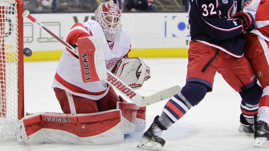 Detroit Red Wings' Jimmy Howard, left, makes a save against Columbus Blue Jackets' Adam Cracknell during the second period of an NHL hockey game Tuesday, Nov. 18, 2014, in Columbus, Ohio. (AP Photo/Jay LaPrete)