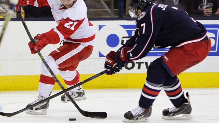 Detroit Red Wings' Tomas Tatar, left, tries to shoot the puck past Columbus Blue Jackets' Jack Johnson during the third period of an NHL hockey game Tuesday, Nov. 18, 2014, in Columbus, Ohio. The Red Wings beat the Blue Jackets 5-0. (AP Photo/Jay LaPrete)