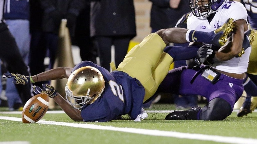 Notre Dame wide receiver Chris Brown (2) fumbles the ball as he is tackled by Northwestern safety Ibraheim Campbell (24) during the second half of an NCAA college football game in South Bend, Ind., Saturday, Nov. 15, 2014. Northwestern won 43-40 in overtime. (AP Photo/Nam Y. Huh)