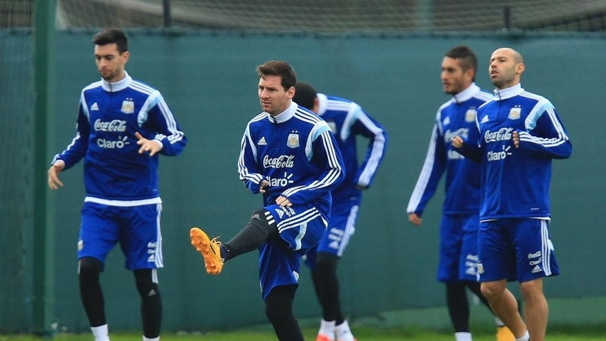 Argentina's soccer star Lionel Messi, centre, stretches during a training session with teammates in  Carrington, Manchester England Monday Nov. 17, 2014.  Argentina will play Portugal in a friendly international soccer match at Old Trafford stadium in Manchester on Tuesday. (AP Photo/Mike Egerton/PA) UNITED KINGDOM OUT