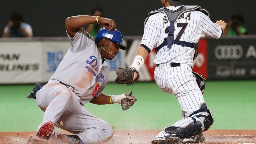 MLB All-Stars Yasiel Puig is tagged out by Japan's catcher Motohiro Shima at home in the sixth inning at Game-5 of their exhibition baseball series at Sapporo Dome in Sapporo, northern Japan, Tuesday, Nov. 18, 2014. (AP Photo/Kyodo News) JAPAN OUT, CREDIT MANDATORY