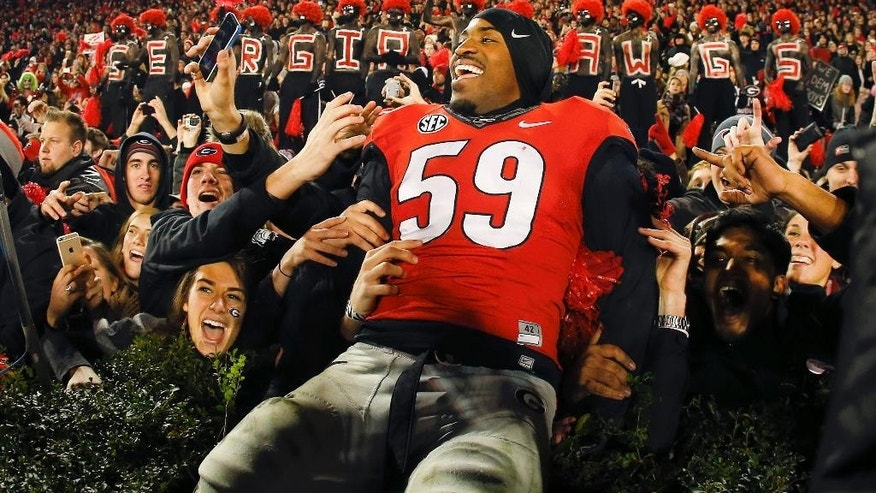Georgia linebacker Jordan Jenkins (59) celebrates with fans after defeating Auburn 34-7 in an NCAA college football game Saturday, Nov. 15, 2014, in Athens, Ga. (AP Photo/John Bazemore)