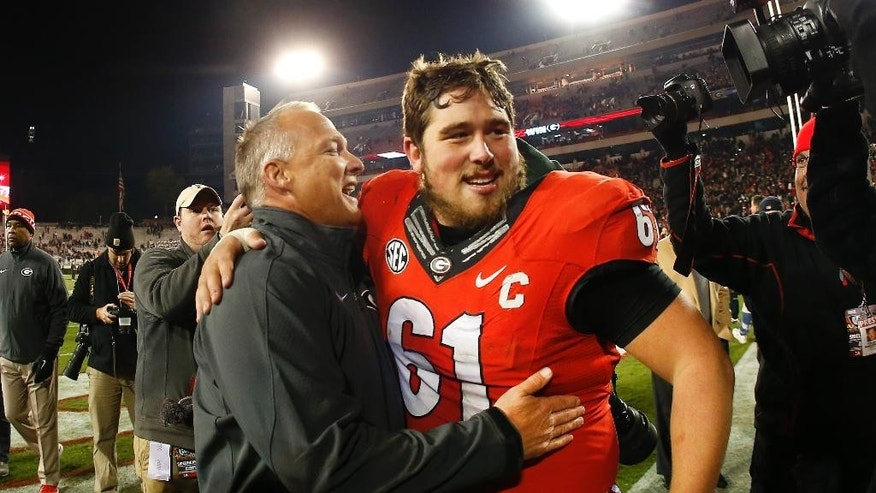 Georgia head coach Mark Richt embraces Georgia center David Andrews (61) after defeating Auburn 34-7 in an NCAA college football game Saturday, Nov. 15, 2014, in Athens, Ga. (AP Photo/John Bazemore)