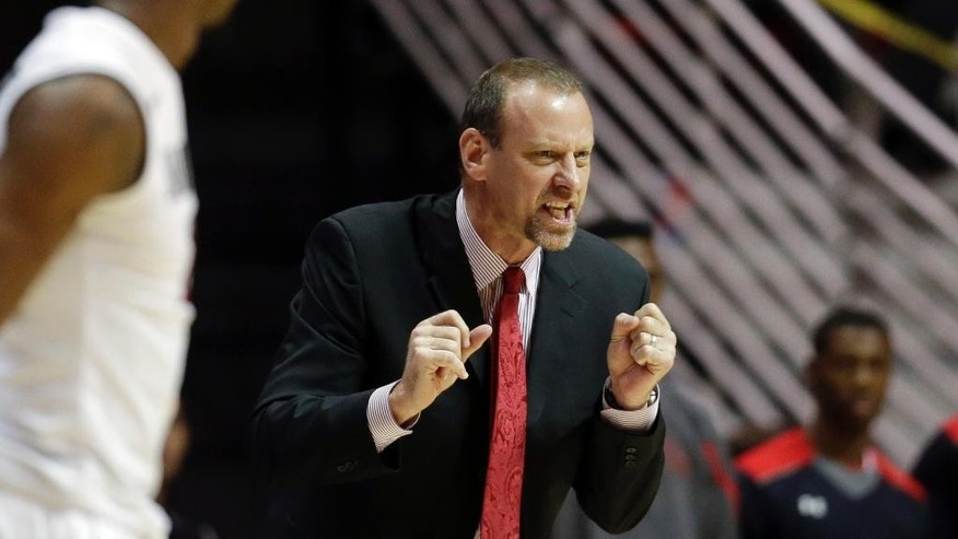 Utah head coach Larry Krystkowiak reacts as the Utes play San Diego State during the first half of an NCAA college basketball game Tuesday, Nov. 18, 2014, in San Diego. (AP Photo/Gregory Bull)