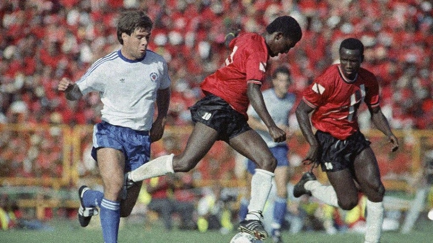 FILE - In this Nov. 19, 1989, file photo, Paul Caligiuri, left, of the United States, and Russell Letepy, center, of Trinidad and Tobago fight for control of the ball at National Stadium in Port-of-Spain, Trinidad. At right is Philbert Jones of Trinidad and Tobago.  The U.S. had failed to qualify for nine straight World Cups since 1950. The North American Soccer League had folded after the 1984 season, and the U.S. Soccer Federation had left its longtime office in the Empire State Building to save money. And then Caligiuri lofted a 28-yard left-footed shot into the net at Port-of-Spain's National Stadium in the 30th minute, That goal gave the United States a 1-0 win over Trinidad and Tobago and put the Americans back among soccer's elite for the first time in several generations. (AP Photo/Mark Lennihan, File)