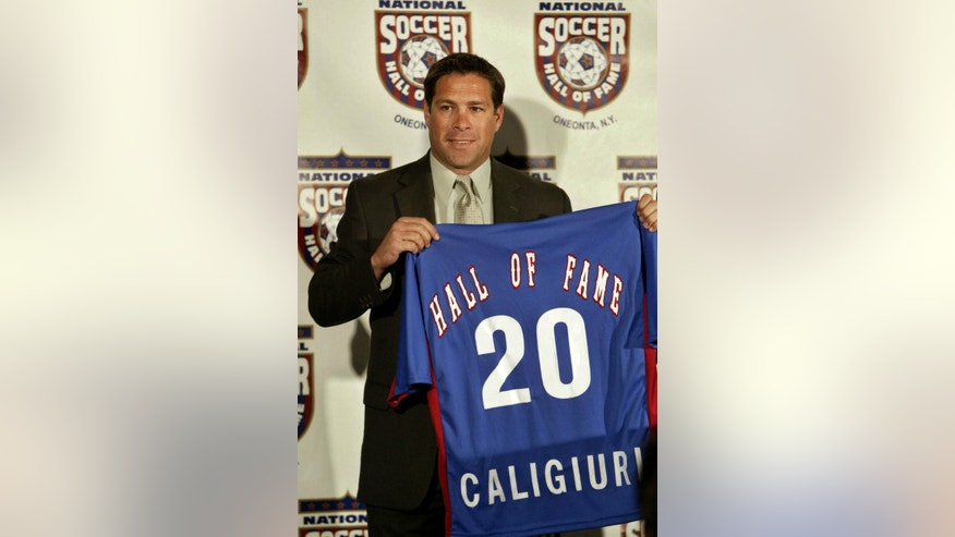 FILE - This May 5, 2004, file photo shows Paul Caligiuri displaying his Hall of Fame jersey at a news conference in Carson, Calif. Twenty-five years ago Wednesday, Nov. 19, Paul Caligiuri changed the direction of American soccer. His left-footed shot into the net at Port-of-Spain's National Stadium that gave the United States a 1-0 win over Trinidad and Tobago put the Americans back among soccer's elite for the first time in several generations. (AP Photo/Ric Francis, File)