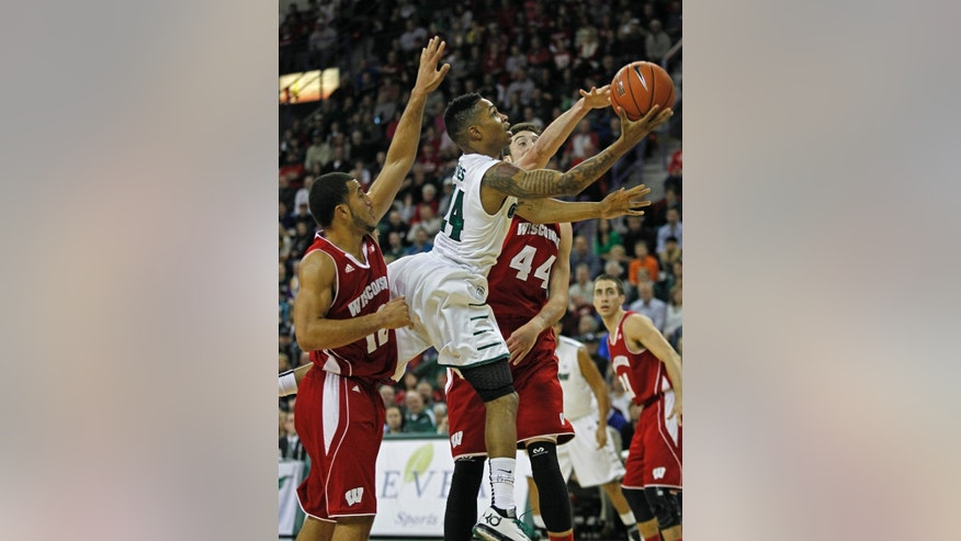 FILE - In this Nov. 16, 2013, file photo, Green Bay's Keifer Sykes drives to the hoop while being guarded by Wisconsin's Traevon Jackson (12) and Frank Kaminsky (44) during the first half of an NCAA college basketball game in Green Bay, Wisc.  In Titletown, Wisconsin-Green Bay guard Keifer Sykes is kind of a big deal. (AP Photo/Matt Ludtke, File)