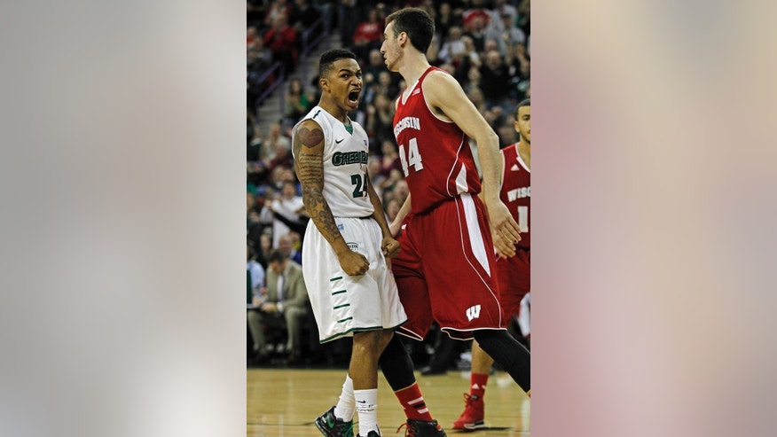 FILE - In this Nov. 16, 2013, file photo, Green Bay's Keifer Sykes, left, reacts in front of Wisconsin's Frank Kaminsky after dunking on the first possession against Wisconsin during the first half of an NCAA college basketball game in Green Bay, Wisc.  In Titletown, Wisconsin-Green Bay guard Keifer Sykes is kind of a big deal. (AP Photo/Matt Ludtke, File)