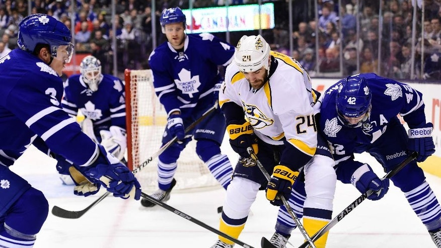 Toronto Maple Leafs' Tyler Bozak (42) and Nashville Predators' Eric Nystrom (24) vie for the puck as Maple Leafs' Cody Franson (4) and Dion Phaneuf (3) watch during the first period of an NHL hockey game Tuesday, Nov. 18, 2014, in Toronto. (AP Photo/The Canadian Press, Frank Gunn)