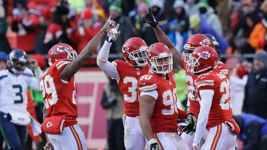 Kansas City Chiefs players including Kansas City Chiefs inside linebacker Josh Mauga (90) celebrate after Kansas City Chiefs cornerback Sean Smith, right, broke up a pass intended for Seattle Seahawks wide receiver Paul Richardson, unseen, at the end of an NFL football game in Kansas City, Mo., Sunday, Nov. 16, 2014. The Kansas City Chiefs won 24-20. (AP Photo/Charlie Neibergall)