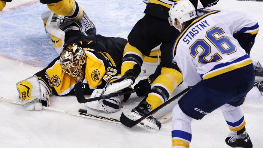 Boston Bruins goalie Tuukka Rask (40), of Finland, dives from the crease to make a save as St. Louis Blues center Paul Stastny (26) looks for the rebound during the third period of an NHL hockey game in Boston, Tuesday, Nov. 18, 2014. (AP Photo/Charles Krupa)
