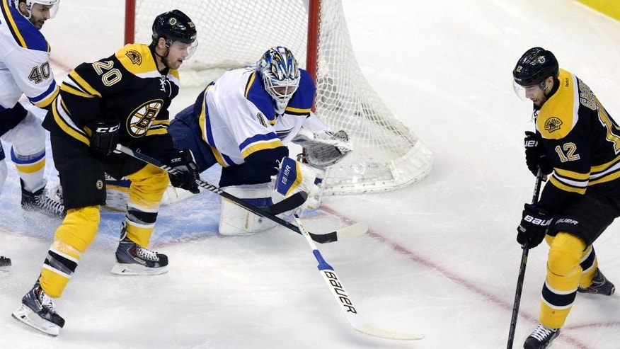 St. Louis Blues goalie Brian Elliott (1) tries to poke the puck away from Boston Bruins left wing Simon Gagne (12) during the first period of an NHL hockey game in Boston, Tuesday, Nov. 18, 2014.  At left is Boston Bruins left wing Daniel Paille. (AP Photo/Charles Krupa)