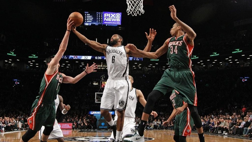 Milwaukee Bucks forward Ersan Ilyasova (7) gets a hand on the ball held by Brooklyn Nets guard Alan Anderson (6) with Bucks guard Giannis Antetokounmpo (34) defending during the first half of an NBA basketball game Wednesday, Nov. 19, 2014, in New York. (AP Photo/Kathy Willens)