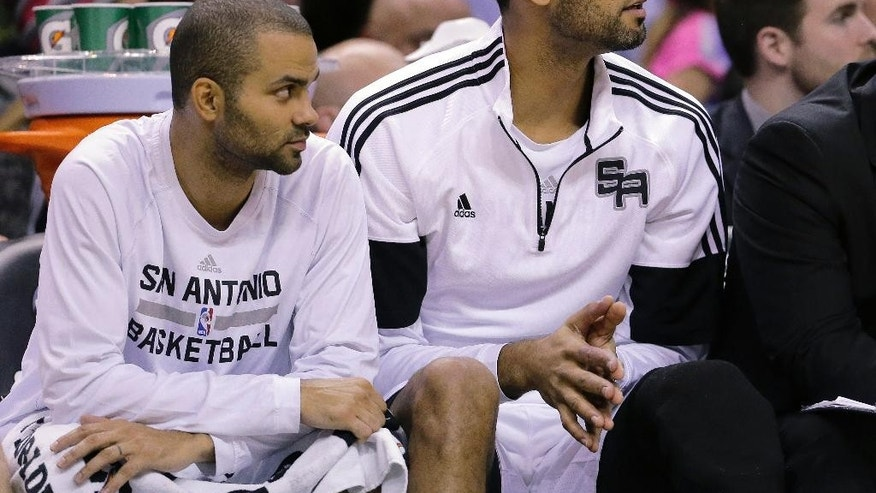 San Antonio Spurs' Tony Parker, left, and Tim Duncan, right, watch from the bench during the first half of an NBA basketball game against the Philadelphia 76ers, Monday, Nov. 17, 2014, in San Antonio. (AP Photo/Eric Gay)