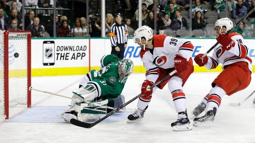 Dallas Stars' Kari Lehtonen (32) of Finland is unable to stop a score by Carolina Hurricanes' Patrick Dwyer (39) as Jay McClement (18) watches in the second period of an NHL hockey game, Tuesday, Nov. 18, 2014, in Dallas. (AP Photo/Tony Gutierrez)