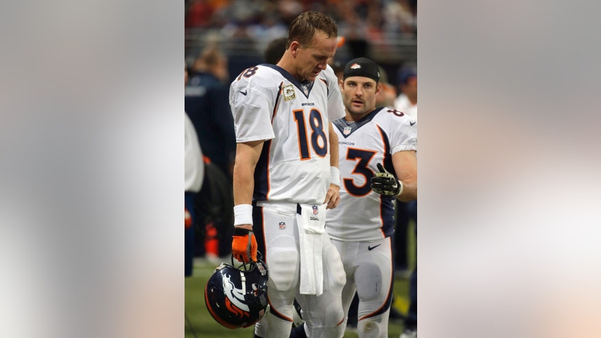 Denver Broncos quarterback Peyton Manning (18) stands in the bench area with teammate Wes Welker during the fourth quarter of an NFL football game against the St. Louis Rams, Sunday, Nov. 16, 2014, in St. Louis. The Rams won 22-7. (AP Photo/Charlie Riedel)