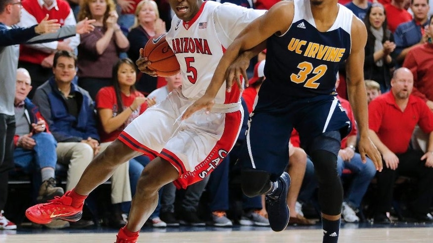 Arizona forward Stanley Johnson (5), left, and UC Irvine guard Aaron Wright (32) battle for the ball during the second half during an NCAA college basketball game, Wednesday, Nov. 19, 2014, in Tucson, Ariz. (AP Photo/Rick Scuteri)