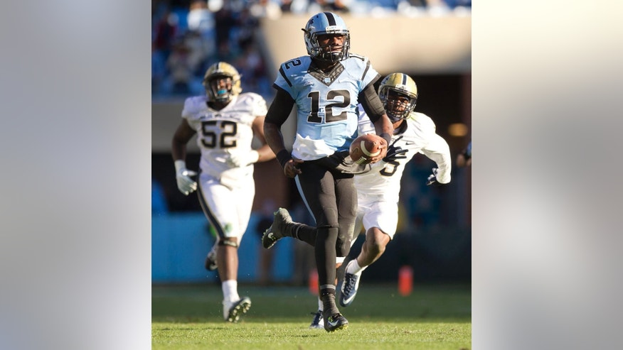 North Carolina quarterback Marquise Williams (12) races ahead of Pittsburgh's Reggie Mitchell (15) for a 45-yard touchdown in the fourth quarter of an NCAA college football game on  Saturday, Nov. 15, 2014, in Chapel Hill, N.C. (AP Photo/The News & Observer, Rovert Willett) MANDATORY CREDIT