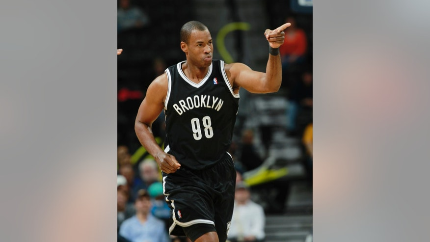 FILE - In this Feb. 27, 2014, file photo, Brooklyn Nets center Jason Collins acknowledges the cheers from his teammates after Collins hit a basket against the Denver Nuggets late in the fourth quarter of the Nets' 112-89 victory in an NBA basketball game in Denver. Collins, the NBA's first openly gay player, announced his retirement on Wednesday, Nov. 19, 2014. (AP Photo/David Zalubowski, File)