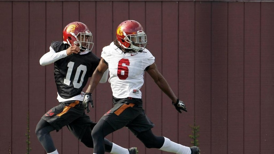 Southern California defensive back Josh Shaw (6) takes part in football team practice with an unidentified member of the practice squad on the campus in Los Angeles Wednesday, Nov. 19, 2014. USC has reinstated Shaw, who had been suspended since he lied to school officials about how he sprained his ankles in a preseason fall. USC announced Shaw's reinstatement Tuesday night, but coach Steve Sarkisian hasn't decided whether the senior will play against No. 11 UCLA on Saturday. (AP Photo/Nick Ut)