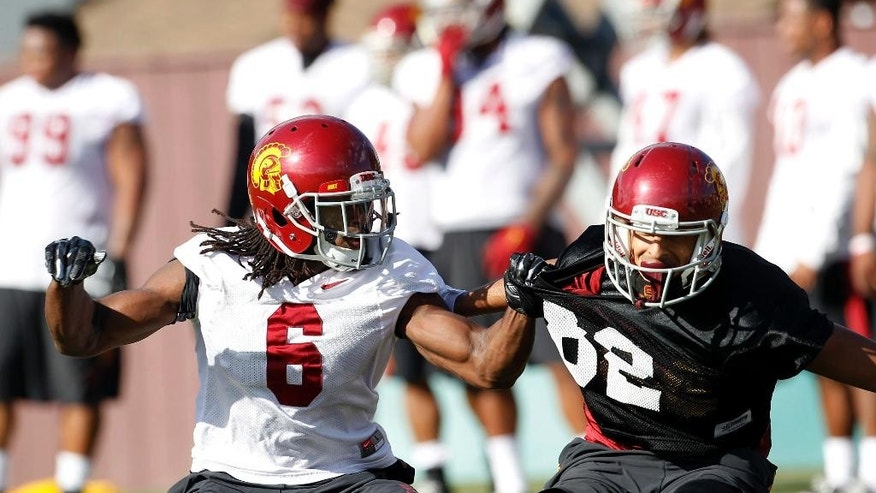 Southern California defensive back Josh Shaw (6) takes part in football team practice with an unidentified member of the practice squad on the campus in Los Angeles Wednesday, Nov. 19, 2014. USC has reinstated Shaw, who had been suspended since he lied to school officials about how he sprained his ankles in a preseason fall.  (AP Photo/Nick Ut)