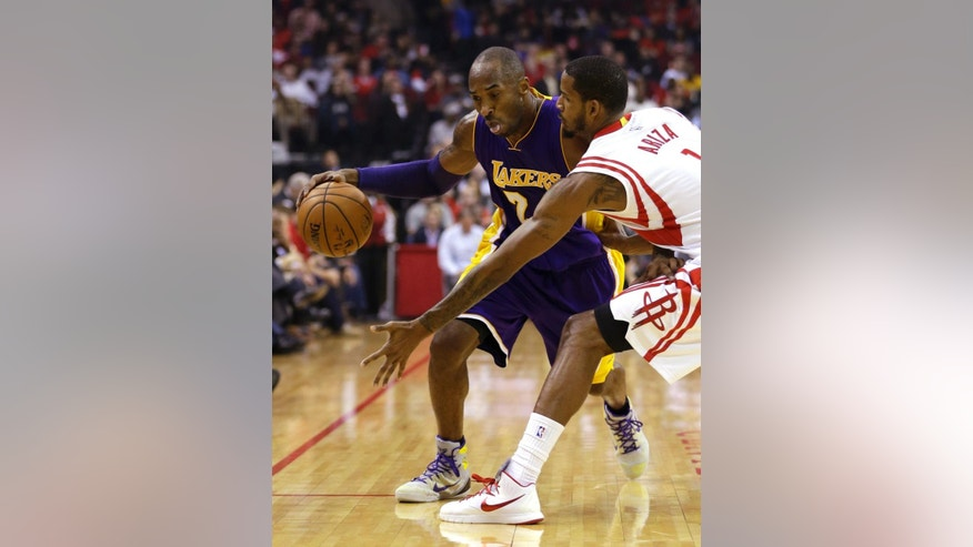 Los Angeles Lakers' Kobe Bryant, left, drives toward Houston Rockets' Trevor Ariza (1) during the first quarter of an NBA basketball game Wednesday, Nov. 19, 2014, in Houston. (AP Photo/David J. Phillip)
