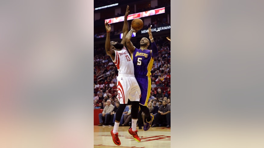 Los Angeles Lakers' Carlos Boozer (5) shoots as Houston Rockets' James Harden (13) defends during the first quarter of an NBA basketball game Wednesday, Nov. 19, 2014, in Houston. (AP Photo/David J. Phillip)