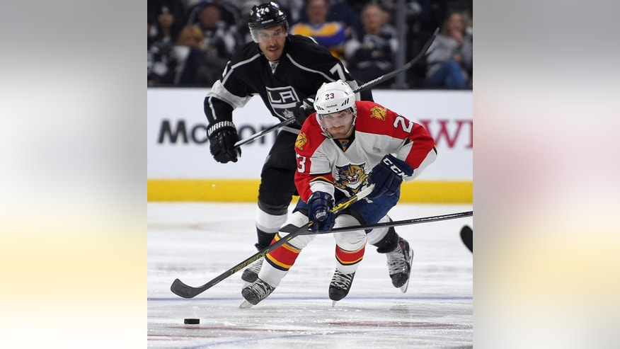 Florida Panthers Rocco Grimaldi, right, moves the puck as Los Angeles Kings left wing Dwight King gives chase during the third period of an NHL hockey game, Tuesday, Nov. 18, 2014, in Los Angeles. The Kings won 5-2. (AP Photo/Mark J. Terrill)