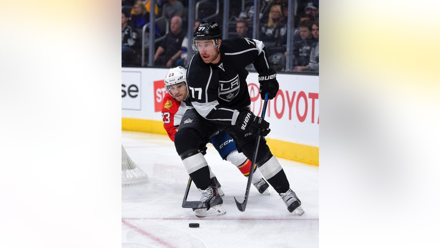 Los Angeles Kings center Jeff Carter, right, moves the puck under pressure from Florida Panthers Rocco Grimaldi during the first period of an NHL hockey game, Tuesday, Nov. 18, 2014, in Los Angeles. (AP Photo/Mark J. Terrill)