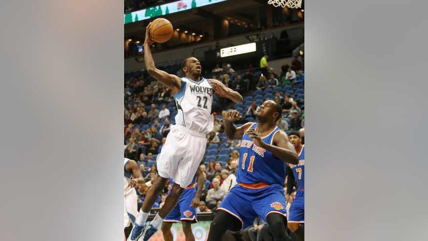 Minnesota Timberwolves' Andrew Wiggins, left, attempts to shoot over New York Knicks' Samuel Dalembert, of Haiti, in the first quarter of an NBA basketball game, Wednesday, Nov. 19, 2014, in Minneapolis. (AP Photo/Jim Mone)