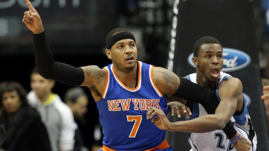 New York Knicks' Carmelo Anthony, left, points for a pass as Minnesota Timberwolves' Andrew Wiggins defends in the first quarter of an NBA basketball game, Wednesday, Nov. 19, 2014, in Minneapolis. (AP Photo/Jim Mone)