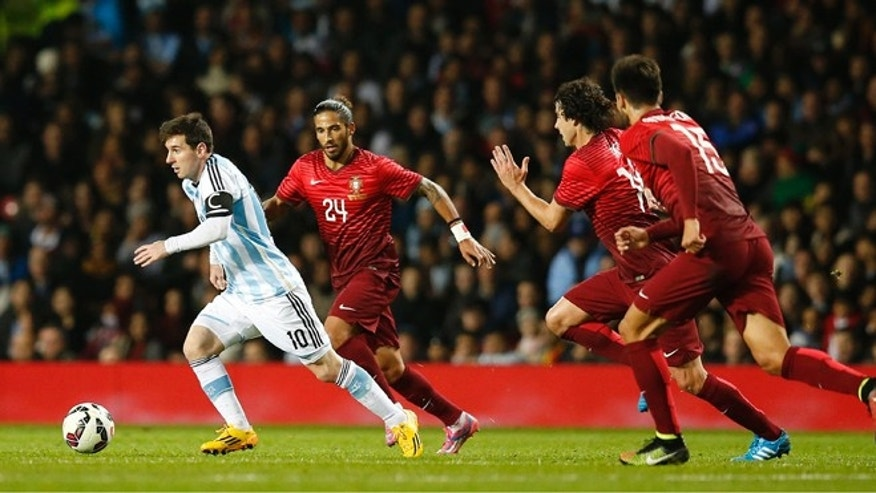 Lionel Messi of Argentina, left, runs clear of the Portugal defence during their International Friendly soccer match at Old Trafford Stadium, Manchester, England, Tuesday Nov. 18, 2014. (AP Photo/Jon Super)