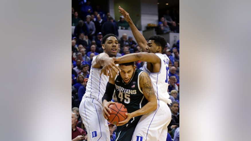 Michigan State's Denzel Valentine, center, is trapped by Duke's Jahlil Okafor, left, and Matt Jones in the second half of an NCAA college basketball game in Indianapolis, Tuesday, Nov. 18, 2014. Duke won 81-71. (AP Photo/Michael Conroy)
