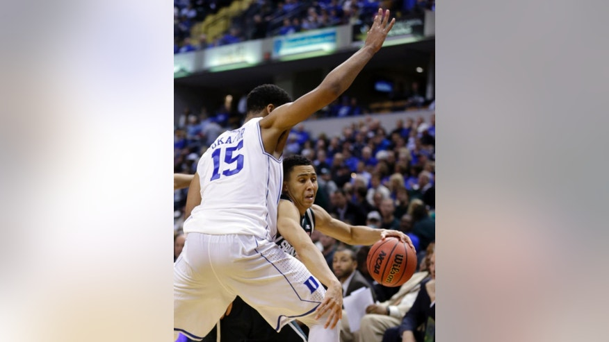 Michigan State's Travis Trice, right, attempts to get past Duke's Jahlil Okafor in the second half of an NCAA college basketball game in Indianapolis, Tuesday, Nov. 18, 2014. Duke won 81-71. (AP Photo/Michael Conroy)