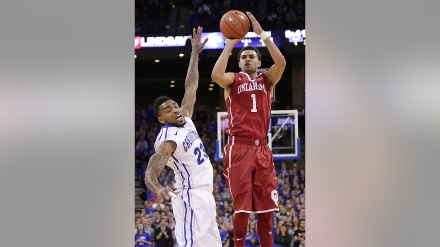 Oklahoma guard Frank Booker (1) shoots over Creighton guard James Milliken (23) during the first half of an NCAA college basketball game in Omaha, Neb., Wednesday, Nov. 19, 2014. (AP Photo/Nati Harnik)