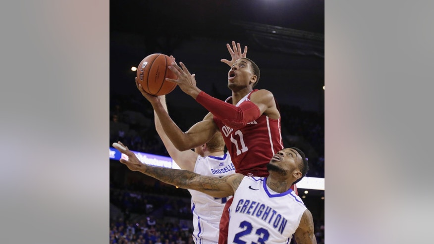 Oklahoma guard Isaiah Cousins (11) goes for a basket against Creighton guard James Milliken (23) and center Geoffrey Groselle, rear, during the first half of an NCAA college basketball game in Omaha, Neb., Wednesday, Nov. 19, 2014. (AP Photo/Nati Harnik)