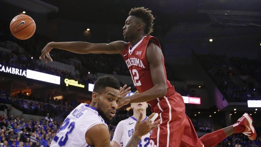 Oklahoma forward Khadeem Lattin (12) tries to reach a rebound against Creighton guard James Milliken (23) and forward Toby Hegner, rear, during the first half of an NCAA college basketball game in Omaha, Neb., Wednesday, Nov. 19, 2014. (AP Photo/Nati Harnik)