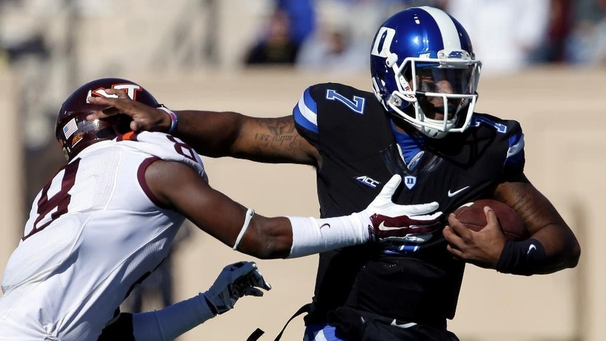 Duke quarterback Anthony Boone (7) runs the ball as Virginia Tech's Detrick Bonner (8) reaches to tackle during the first half of an NCAA college football game in Durham, N.C., Saturday, Nov. 15, 2014. (AP Photo/Gerry Broome)