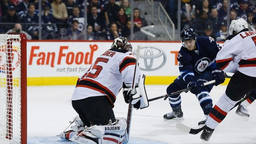 Winnipeg Jets' Mark Scheifele (55) scores on New Jersey Devils goaltender Cory Schneider (35) during second period NHL action in Winnipeg, on Tuesday, Nov. 18, 2014. (AP Photo/The Canadian Press, John Woods)