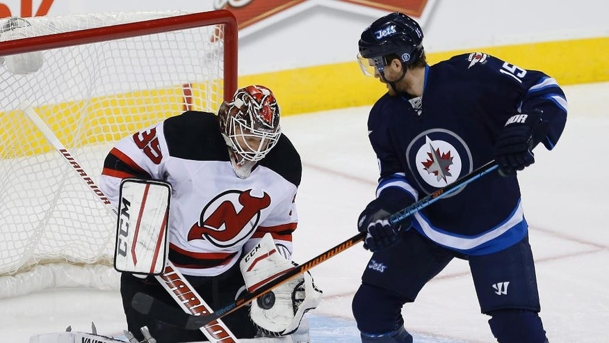 New Jersey Devils goaltender Cory Schneider (35) stops the deflection by Winnipeg Jets' Matt Halischuk (15) during first period NHL action in Winnipeg, Manitoba, on Tuesday, Nov. 18, 2014. (AP Photo/The Canadian Press, John Woods)