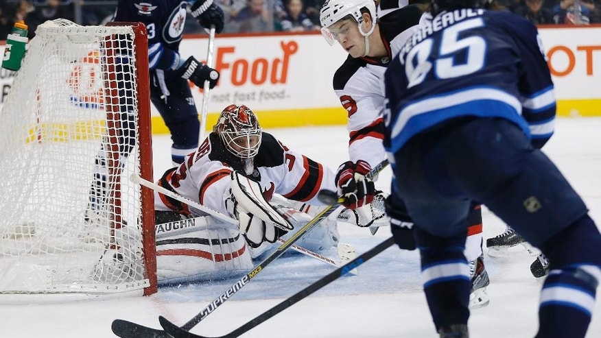 New Jersey Devils goaltender Cory Schneider (35) knocks the puck away as Winnipeg Jets' Mark Scheifele (55) looks for the rebound and Devils' Damon Severson (28) defends during second period NHL action in Winnipeg, Manitoba, on Tuesday, Nov. 18, 2014. (AP Photo/The Canadian Press, John Woods)