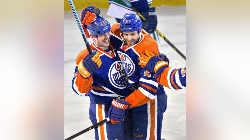 Edmonton Oilers' Matt Hendricks (23) and Boyd Gordon (27) celebrate a goal against the Vancouver Canucks during the second period of an NHL hockey game Wednesday, Nov. 19, 2014, in Edmonton, Alberta. (AP Photo/The Canadian Press, Jason Franson)