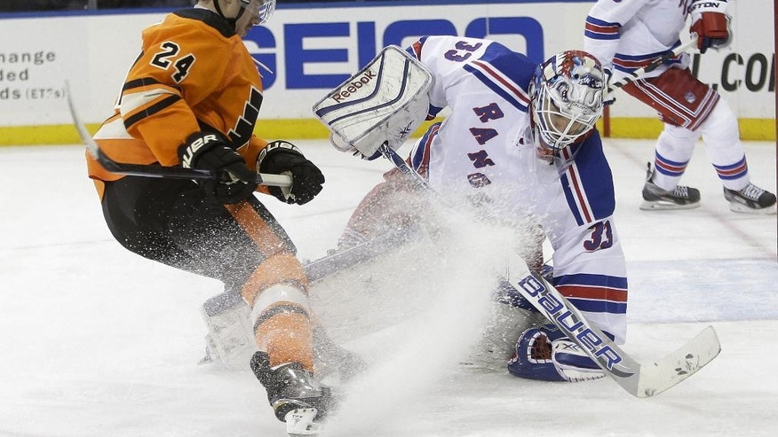 New York Rangers goalie Cam Talbot (33) protects the puck from Philadelphia Flyers' Matt Read (24) during the first period of an NHL hockey game Wednesday, Nov. 19, 2014, in New York. (AP Photo/Frank Franklin II)