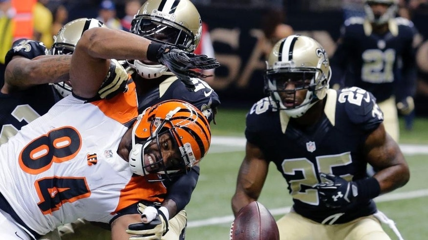 Cincinnati Bengals running back Jeremy Hill (32) carries as New Orleans Saints inside linebacker David Hawthorne (57) tackles in the second half of an NFL football game in New Orleans, Sunday, Nov. 16, 2014. The Bengals won 27-10.  (AP Photo/Rogelio Solis)