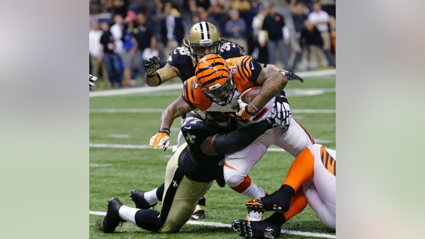 Cincinnati Bengals running back Jeremy Hill (32) carries as New Orleans Saints nose tackle Brodrick Bunkley (77) tackles in the first half of an NFL football game in New Orleans, Sunday, Nov. 16, 2014. (AP Photo/Bill Haber)