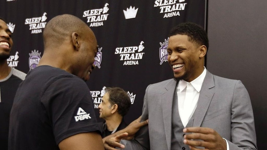 Sacramento Kings forward Rudy Gay, right, is congratulated by teammate Carl Landry after talking with reporters about the three-year, $40 million contract extension he signed with the Kings, at a news conference in Sacramento, Calif., Wednesday, Nov. 19, 2014. Gay, 28, is currently in his ninth NBA season and was acquired by the Kings in a trade last year with Toronto Raptors. (AP Photo/Rich Pedroncelli)