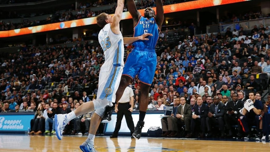 Oklahoma City Thunder center Kendrick Perkins, right, goes up to shoot against Denver Nuggets center Timofey Mozgov, of Russia, in the first quarter of an NBA basketball game in Denver, Wednesday, Nov. 19, 2014. (AP Photo/David Zalubowski)