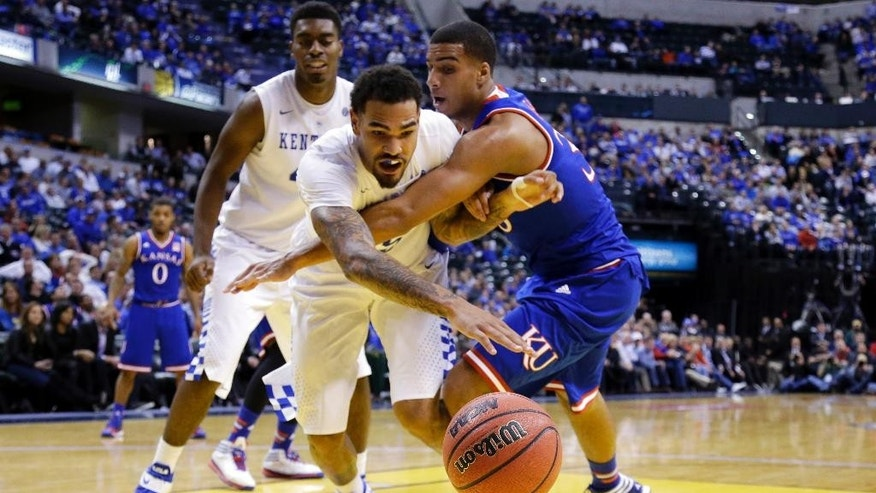 Kentucky's Willie Cauley-Stein, left, and Kansas's Landen Lucas battle for a loose ball in the second half of an NCAA college basketball game in Indianapolis, Tuesday, Nov. 18, 2014. Kentucky defeated Kansas 72-40. (AP Photo/Michael Conroy)