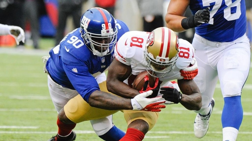 New York Giants defensive end Jason Pierre-Paul (90) tackles San Francisco 49ers wide receiver Anquan Boldin (81) during the first half of an NFL football game Sunday, Nov. 16, 2014, in East Rutherford, N.J.  (AP Photo/Bill Kostroun)